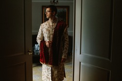 A beautiful and calm white man is preparing for his indian wedding