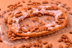 A beautiful and tasty Kringle covered with almonds with the tray on a red oak surface.