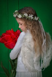 A beautiful angel girl in white clothes, white feather wings and wreath of natural of cherry flowers on her head holding large bouquet of fresh red tulips in her hands.