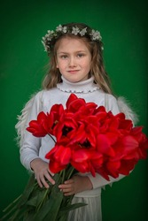 A beautiful angel girl in white clothes, white feather wings and wreath of natural of cherry flowers on her head holding big bouquet of fresh red tulips in her hands.