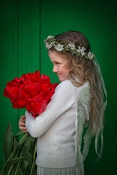 A beautiful angel girl in white clothes, white feather wings and wreath of natural of cherry flowers on her head smiling and holding large bouquet of fresh red tulips in her hands.
