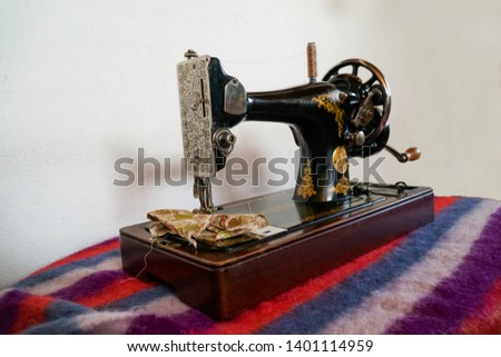 A beautiful antique sewing machine on a mohair blanket.