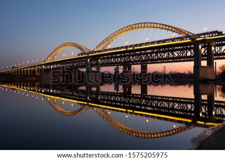 A beautiful arch bridge with light is reflected in the river with smooth water against the background of the city of Nizhny Novgorod Сток-фото ©