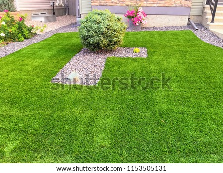 A beautiful artificial lawn in the front yard with nice flowers and shrubs surrounding it #1153505131