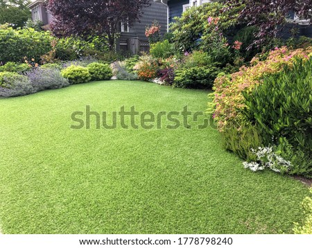 A beautiful artificial lawn in the front yard with nice flowers and shrubs surrounding it Foto stock ©