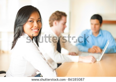 A beautiful Asian business woman smiling looking over shoulder at camera meeting with two male colleagues team members sitting at conference room table. Horizontal