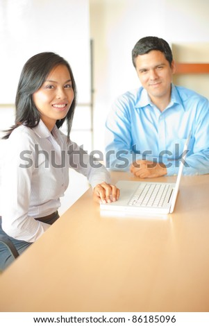 A beautiful Asian businesswoman meets with a handsome hispanic businessman