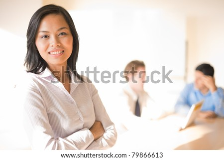 A beautiful asian businesswoman smiling in front of her working colleagues