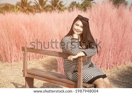 A beautiful Asian fat female poses sitting with pink dry trees in the background in the public park. Stock photo ©
