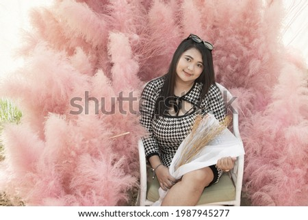 A beautiful asian fat woman sitting pose there is a fuffy pink dry tree in the background in the public park. Stock photo ©