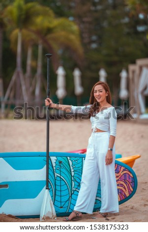 a beautiful asian girl stand in relaxing on vacation by wearing white dress beside kayaks with relax on the beach. in relax concept smile day
