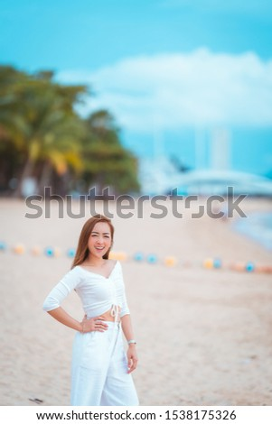 a beautiful asian girl stand in relaxing on vacation by wearing white dress with relax on the beach. in relax concept smile day