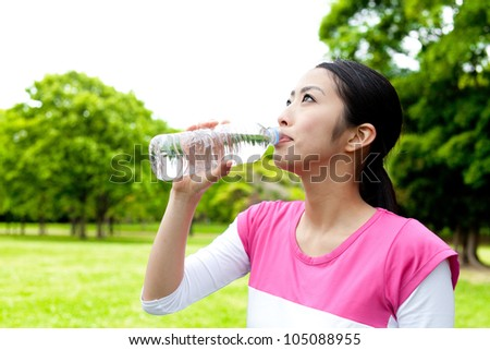 a beautiful asian woman drinking water in the park