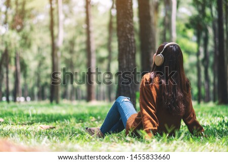 A beautiful asian woman enjoy listening to music with headphone with feeling happy and relaxed in the park #1455833660