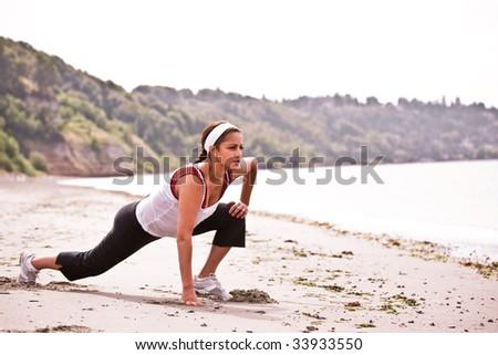 A beautiful asian woman exercises at a beach