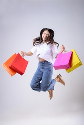 A beautiful Asian woman holding shopping bags of various colors and jumping with a happy expression on a white background. Holiday Shopping.