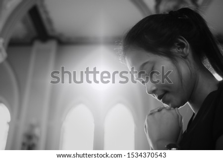 A beautiful Asian woman is praying to God with His blessing for a better life in a Christian church in Chanthaburi province. The concept of forgiveness and belief in goodness.Monochrome picture.
