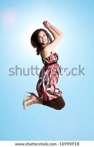 A beautiful asian woman jumping for joy