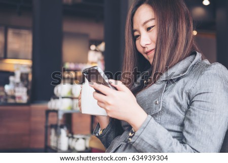 A beautiful asian woman sitting and looking at mobile phone while holding hot coffee cup before drinking in loft cafe #634939304