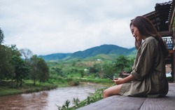 A beautiful asian woman using mobile phone while sitting by the river with mountains and nature background