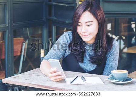 A beautiful asian woman using on the smart phone with feeling relax and smiley face , sitting in loft coffee cafe #552627883