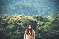A beautiful Asian woman with smiley face standing alone with green nature and mountain background