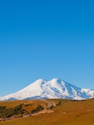 A beautiful asphalt road through the autumn hills of the Caucasus leads to Elbrus. Elbrus with two peaks against the blue sky is covered with snow. Copy space.