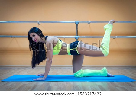 A beautiful athletic girl in the kneeling position doing leg exercises at gymnastic hall background. Dancer dressed in a sporty uniform stretching and exercising on mat. Attractive brunette knelling.