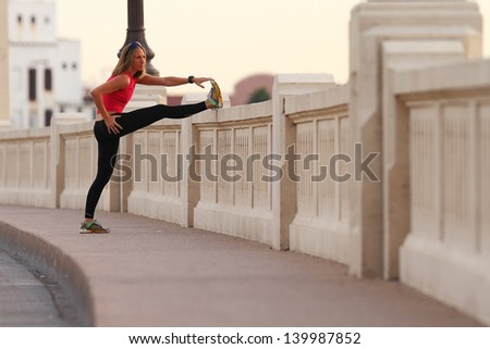 A beautiful athletic woman stretches before running in an urban environment