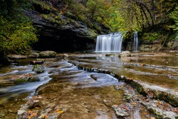 A beautiful autumn forest landscape with idyllic waterfall and river steps