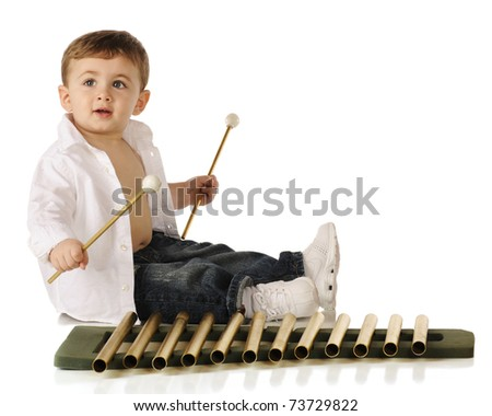 A beautiful baby boy making music with golden xylophone-style pipes.  Isolated on white.