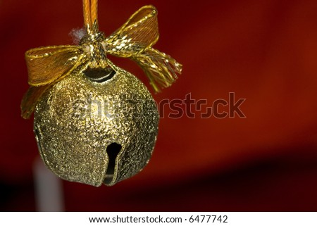 a beautiful background of a gold jingle bell on red background