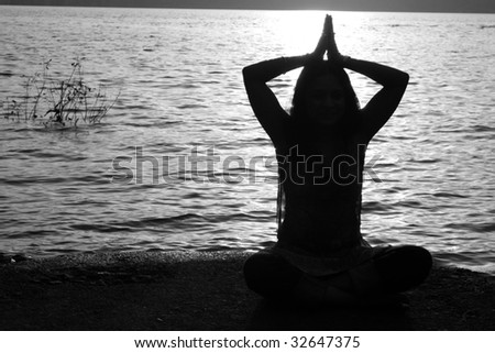 A beautiful background of silhouetted pose of a traditional Indian woman of hindu religion, praying on a backdrop of water ripples.