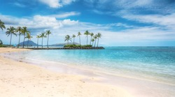 A beautiful beach scene in the Kahala area of Honolulu, with fine white sand, shallow turquoise water, a view of coconut palm trees and Koko Head in the background.