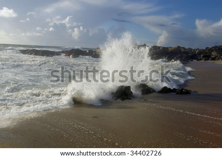 a beautiful beach with waves breaking on the rocks