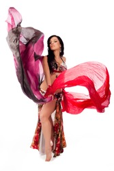 A beautiful bellydancer dances with two colorful, flowing, silk veils. Isolated on a white background. Clipping path included.