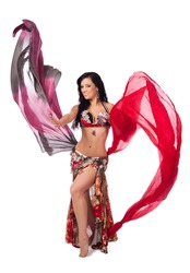 A beautiful bellydancer in a multicolor costume smiles as she dances with two colorful, flowing, silk veils. Isolated on a white background. Clipping path included.