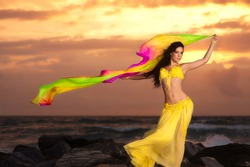 A beautiful bellydancer poses with a flowing multicolor silk veil. She is wearing a yellow costume and standing on a rocky bank in front of the Atlantic Ocean with the sun rising behind her.