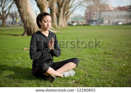 A beautiful black woman doing yoga meditation outdoor in a park