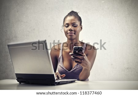 A beautiful black woman is smiling while is using a smart-phone and a laptop computer