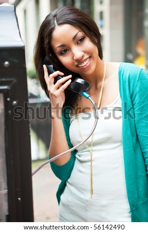 A beautiful black woman talking on the public phone