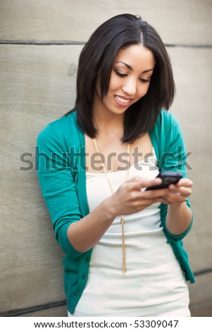 A beautiful black woman texting on her phone