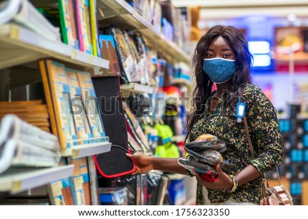 A beautiful Black woman wearing homemade face mask,hand sanitizer bottle tied on her handbag,holding baked snacks,shopping in a supermarket-New normal everyday lifestyle in covid-19 pandemic season
