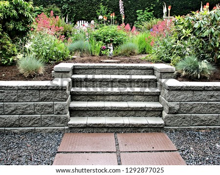 A beautiful block retaining wall in gray color with integrated staircase into existing garden landscaped with perennial flowers and shrubs