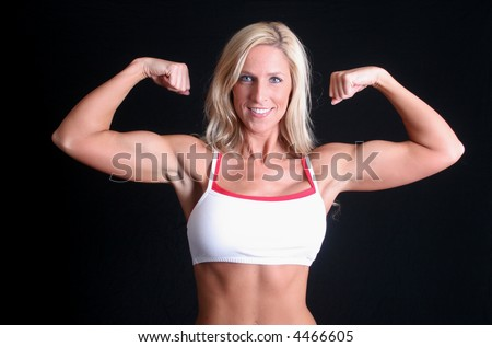 A beautiful blond female body builder is flexing her muscles