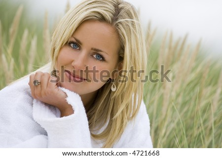 A beautiful blond haired blue eyed model wearing a white toweling robe sits amid tall grass