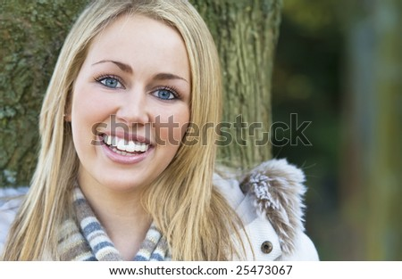 A beautiful blond haired blue eyed model with a beautiful smile shot in woodland surroundings using natural light.