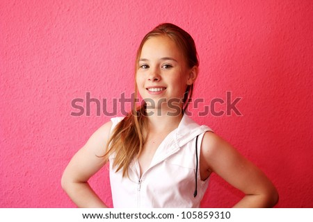 A beautiful blond-haired 13-years old girl, portrait over pink background