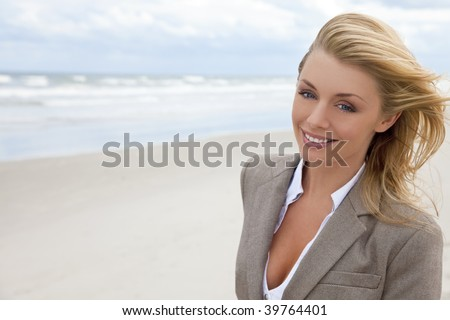 A beautiful blond young woman at the beach illuminated by natural light with her hair blowing in the wind