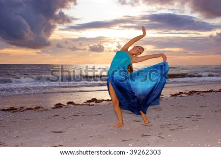 A beautiful blonde ballerina is arching back with her arms up on the beach as the sun sets looking at you the viewer and smiling.